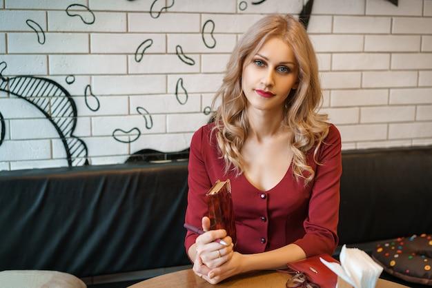 Schöne junge frau, die an einem tisch mit einem notizbuch und einem telefon sitzt.