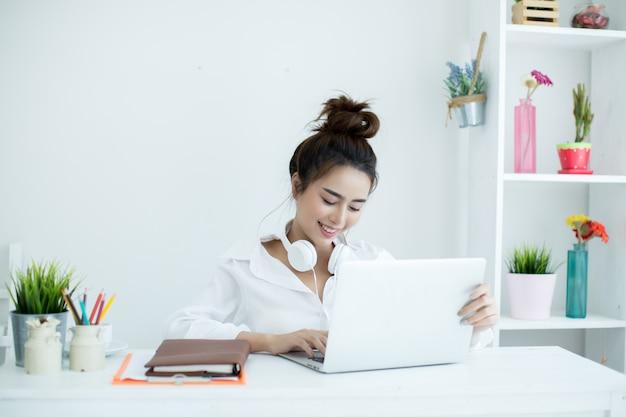 Schöne junge frau, die an ihrem laptop in ihrem raum arbeitet.