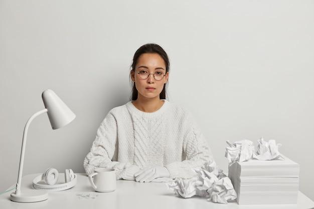 Schöne junge frau, die an ihrem schreibtisch studiert