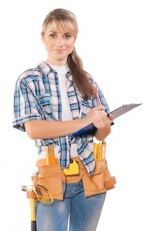 Schöne junge frau, die arbeitskleidung trägt, die zwischenablagestift mit einigen werkzeugen hält