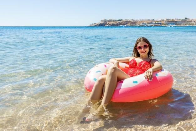 Schöne junge frau, die auf aufblasbarem donut im meer sich entspannt