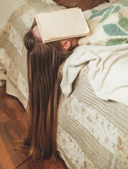Schöne junge frau, die auf bett mit buch bedeckt, das ihr gesicht bedeckt, weil buch mit vorbereitender prüfung des college liest, frau schläfrig mit müde, so dass freizeit, entspannung und bildungskonzept.