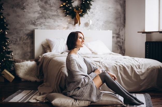 Schöne junge frau, die auf bett nahe weihnachtsbaum sich entspannt