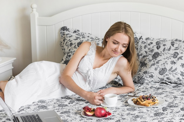 Schöne junge frau, die auf dem bett betrachtet frühstück liegt