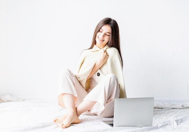 Schöne junge frau, die auf dem boden sitzt und freiberufliches projekt auf laptop, unter verwendung des computers tut