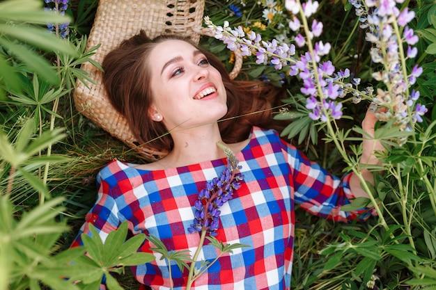 Schöne junge frau, die auf dem feld im grünen gras und in den blumen liegt.