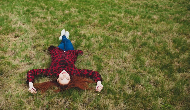 Schöne junge frau, die auf dem feld liegt und auf dem wunderbaren gras sich entspannt