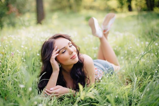 Schöne junge frau, die auf dem gras liegt