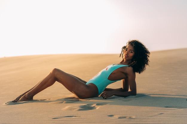 Schöne junge frau, die auf dem sand in den wüstendünen aufwirft