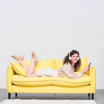 Schöne junge frau, die auf dem sofa genießt musik auf kopfhörer liegt
