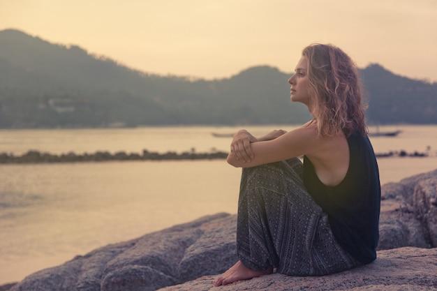 Schöne junge frau, die auf den felsen durch das meer sitzt und den sonnenuntergang aufpasst