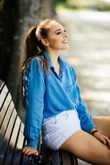 Schöne junge frau, die auf der bank im sommerpark sitzt