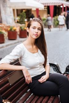 Schöne junge frau, die auf der bank in der altstadt sitzt