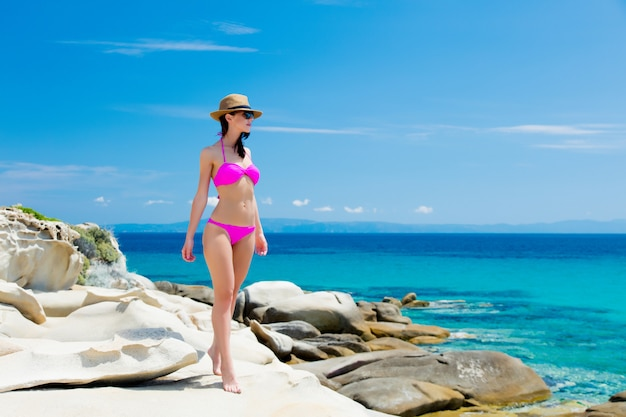 Schöne junge frau, die auf der wunderbaren steinküste in griechenland im badeanzug steht