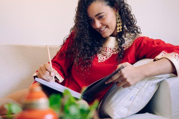 Schöne junge frau, die auf ein notizbuch schreibt und tee zu hause trinkt