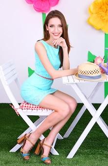 Schöne junge frau, die auf einem stuhl am tisch auf dekorativem hintergrund sitzt