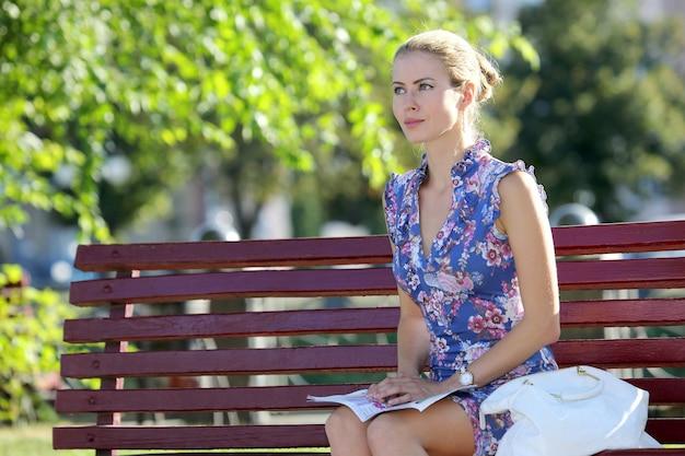 Schöne junge frau, die auf einer bank im park sitzt