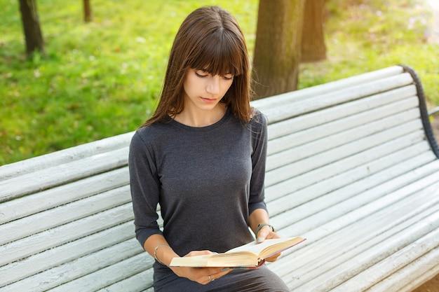 Schöne junge frau, die auf einer bank in der straße ein buch lesend sitzt.