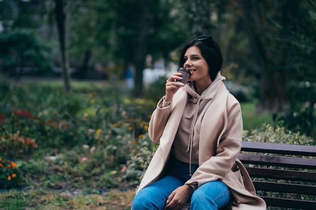 Schöne junge frau, die auf einer bank sitzt, die kaffee im park genießt