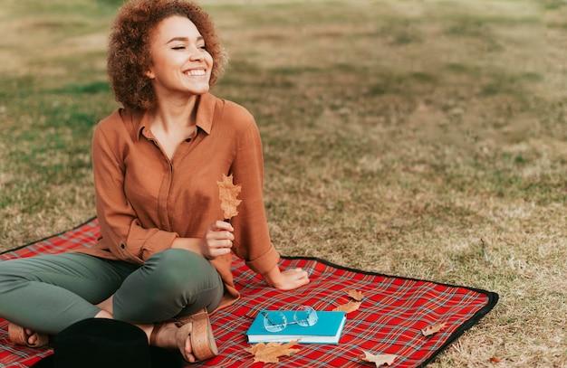 Schöne junge frau, die auf einer picknickdecke sitzt