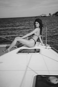 Schöne junge frau, die auf einer yacht aufwirft