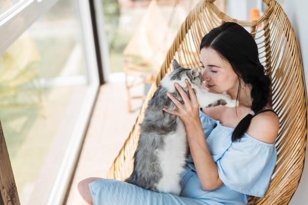 Schöne junge frau, die auf holzstuhl am patio liebt ihre katze sitzt