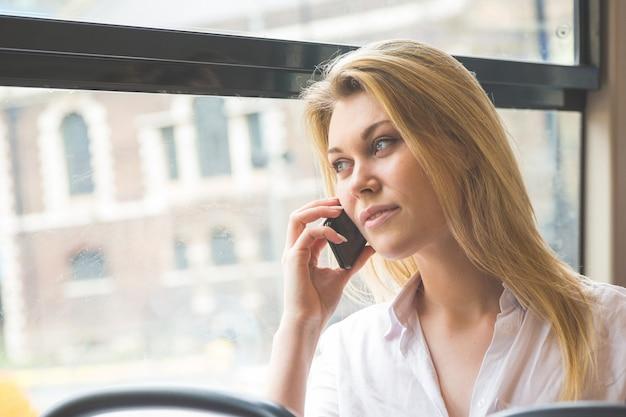 Schöne junge frau, die auf mobile beim austauschen in london spricht