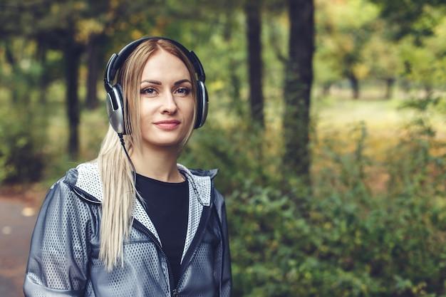 Schöne junge frau, die auf stadtpark, hörend musik auf kopfhörern geht.