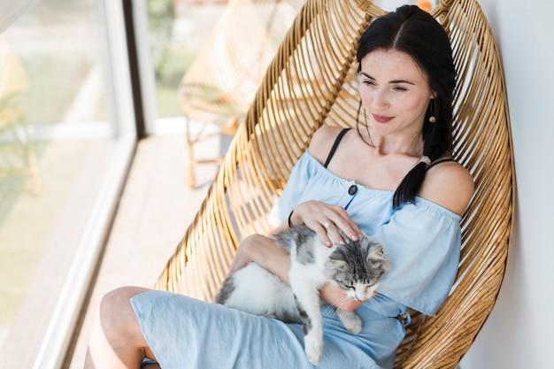Schöne junge frau, die auf stuhl mit ihrer netten katze sitzt