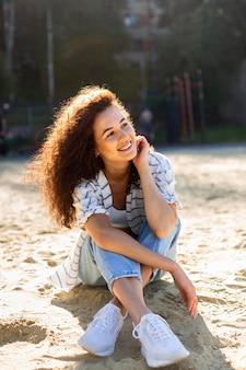 Schöne junge frau, die aufwirft und lächelt