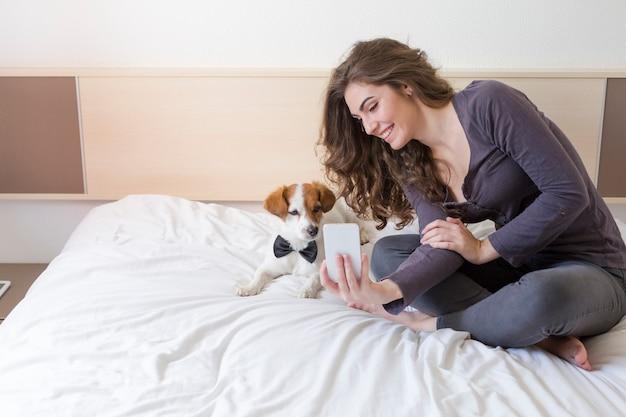 Schöne junge frau, die außerdem ein selfie mit handy auf bett mit ihrem netten kleinen hund nimmt. hund mit fliege. zuhause, drinnen und lifestyle