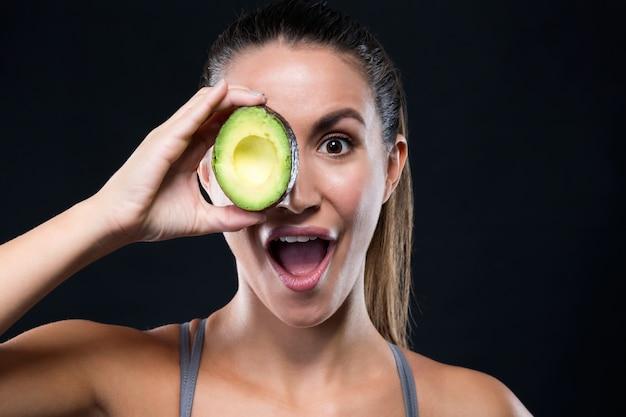 Schöne junge frau, die avocado über schwarzem hintergrund hält.