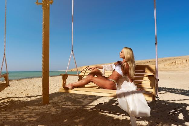 Schöne junge frau, die badeanzug schwingt, der auf einer schaukel während des sonnigen tages im resort schwingt