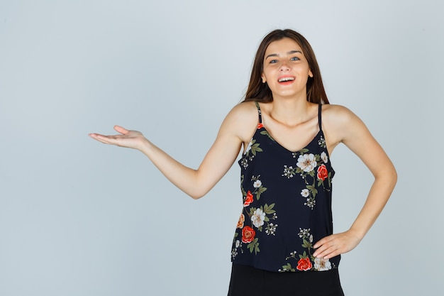 Schöne junge frau, die begrüßungsgeste in bluse zeigt und glücklich schaut