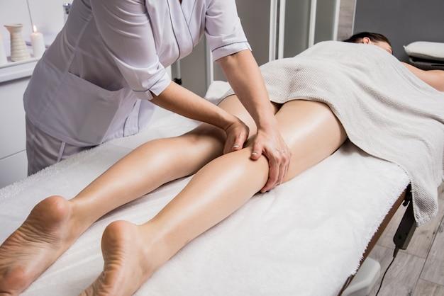 Schöne junge frau, die beinmassage mit öl im spa-salon genießt. kosmetologie