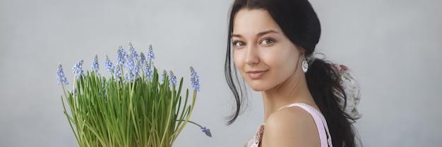 Schöne junge frau, die blumenstrauß von frühlingsblumen hält, die die kamera sinnlich romantisch betrachtet