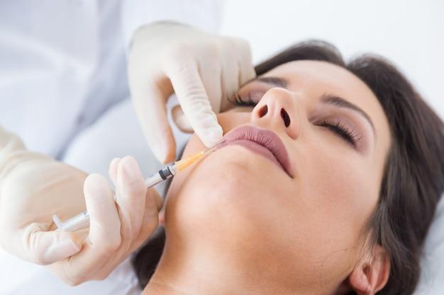 Schöne junge frau, die botox kosmetische einspritzung in ihrem gesicht erhält.