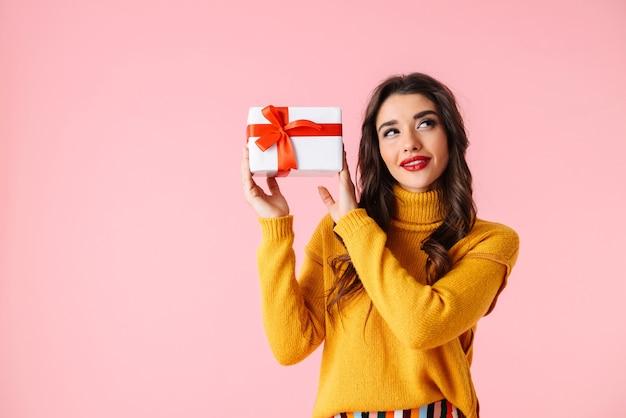 Schöne junge frau, die bunte kleidung trägt, die lokal über rosa steht und geschenkbox hält