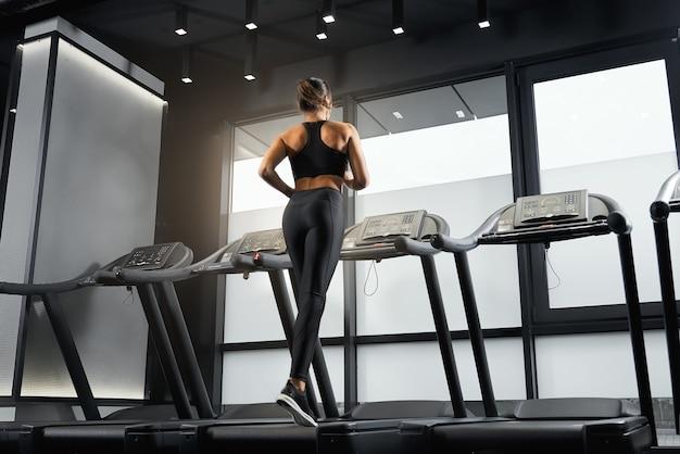 Schöne junge frau, die cardio im fitnessstudio macht