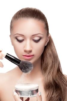 Schöne junge frau, die das pulver auf der bürste aufnimmt. die letzte phase des make-ups