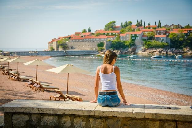 Schöne junge frau, die das seestück und die insel sveti stefan betrachtet. montenegro, europa.