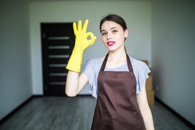 Schöne junge frau, die daumen nach oben zeigt und reinigungsmittel für fenster hält