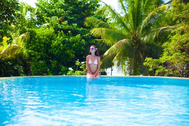 Schöne junge frau, die den ruhigen luxusswimmingpool genießt