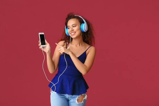 Schöne junge frau, die die musik auf farbhintergrund hört