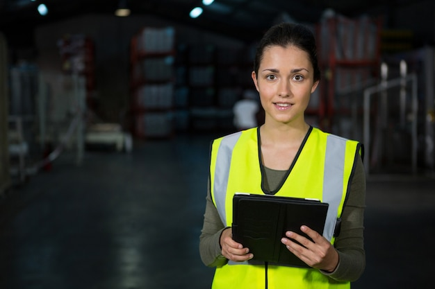 Schöne junge frau, die digitales tablett in der fabrik verwendet