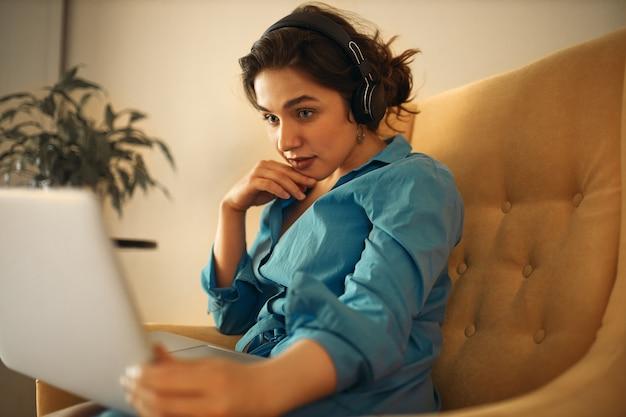 Schöne junge frau, die drahtloses headset verwendet, während webinar auf social-media-marketing, fokussiertes aussehen beobachtet. hübsches mädchen, das online auf der couch mit laptop sitzend lernt und hand am kinn hält
