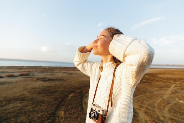 Schöne junge frau, die draußen am strand während des sonnenuntergangs geht und fotos mit fotokamera macht