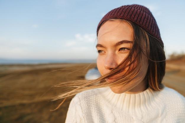 Schöne junge frau, die draußen am strand während des sonnenuntergangs geht