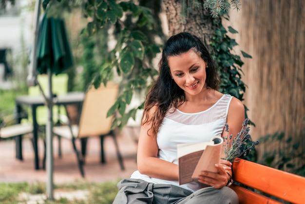 Schöne junge frau, die draußen ein buch auf der bank liest.
