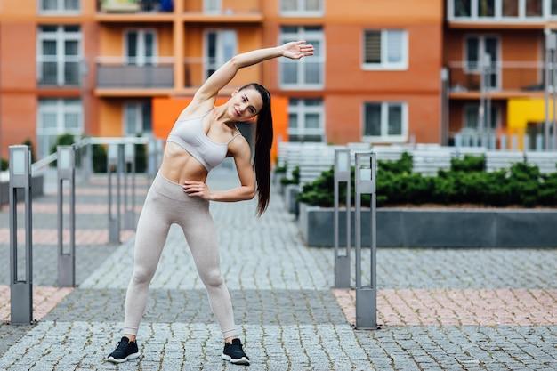 Schöne junge frau, die draußen übungen tut. wunderschöne fitness frau hart trainieren.